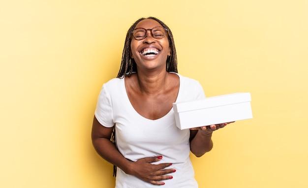 Hardop lachen om een hilarische grap, blij en opgewekt voelen, plezier maken en een lege doos vasthouden