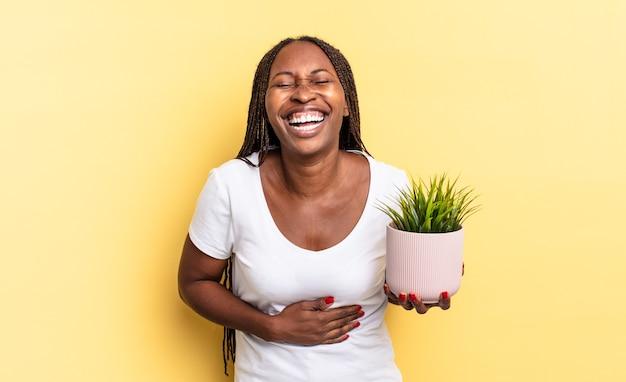 Hardop lachen om een hilarische grap, blij en opgewekt voelen, plezier maken met een plantenpot
