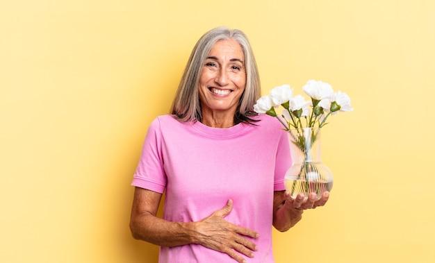 Hardop lachen om een hilarische grap, je blij en opgewekt voelen, plezier hebben met het vasthouden van decoratieve bloemen