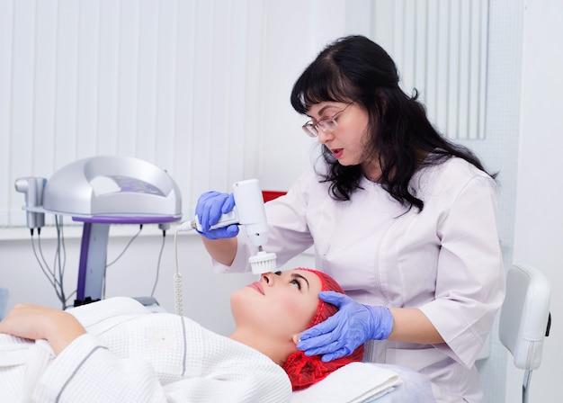 Hardware cosmetologie. de schoonheidsspecialiste voert een mechanische procedure uit om het oppervlak te pellen. borstel de huid schoon.