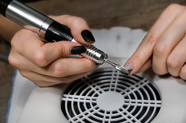 Hardware manicure in schoonheidssalon of thuis. manicure past elektrische nagelvijlboor toe aan manicure op vrouwelijke vingers. mechanische manicure close-up