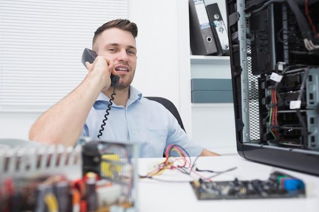Hardware professional zittend door een open cpu tijdens een oproep