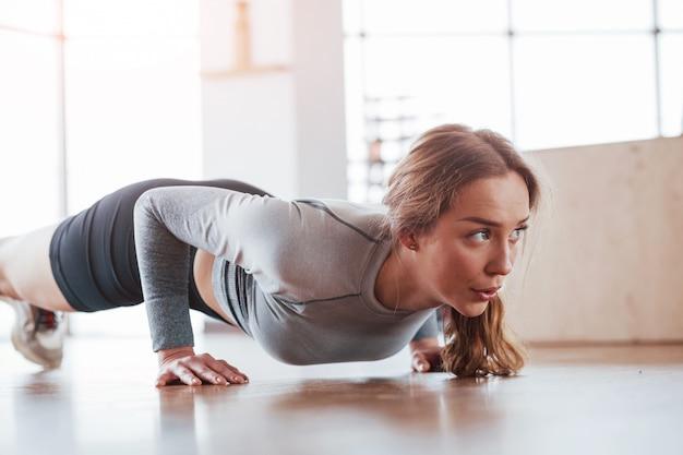 Hardwerkend. sportieve jonge vrouw heeft fitnessdag in de sportschool in de ochtendtijd