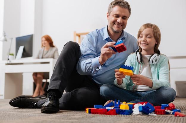 Hardwerkende ambitieuze aardige vader die een minuut vindt om te spelen met zijn dochter die hij vandaag aan het werk zet
