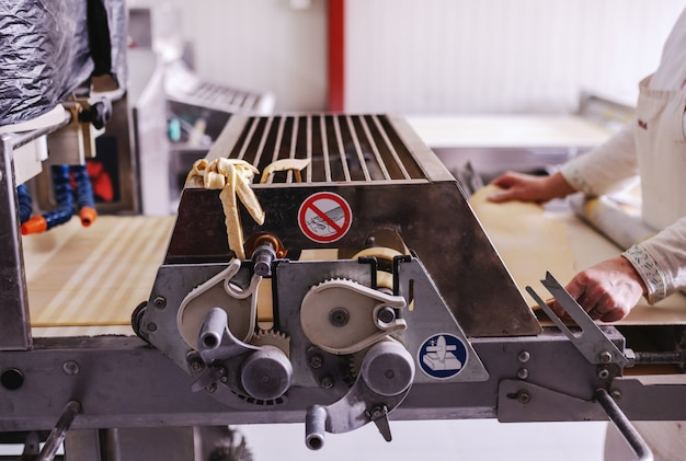 Hardwerkende bakker in wit uniform maken taart korsten op machine in bakkerij.
