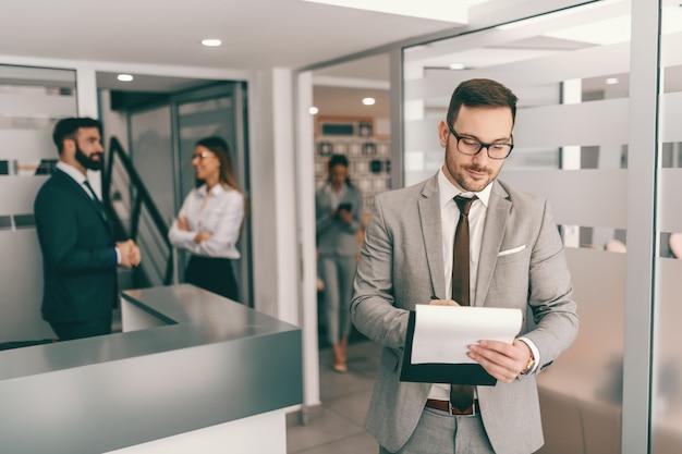 Hardwerkende blanke bebaarde zakenman in formele slijtage ideeën opschrijven op klembord. hoe harder je werkt, hoe succesvol je wordt.