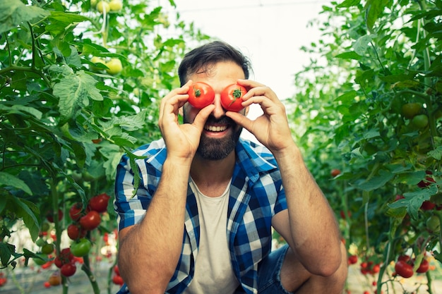 Hardwerkende boer die gekke gezichten met tomatengroenten in de tuin maakt