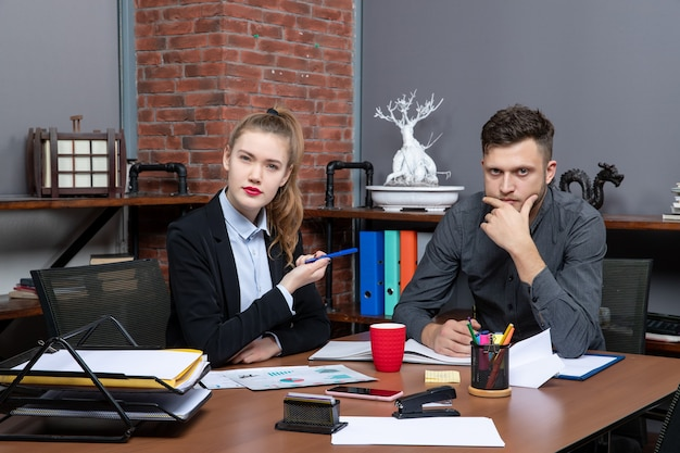 Hardwerkende en drukke professionele werknemers die één probleem bespreken in de documenten op kantoor