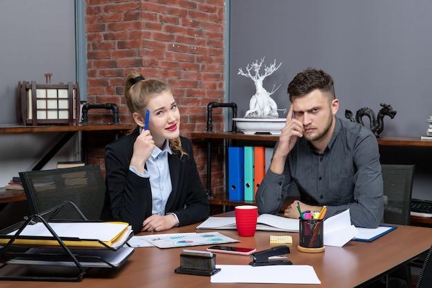 Hardwerkende en verraste professionele werknemers die één probleem bespreken in de documenten op kantoor