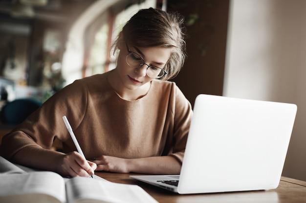 Hardwerkende gerichte vrouw in trendy bril te concentreren op het schrijven van essay, zittend in een gezellig café in de buurt van laptop, werken en zorgvuldig notities maken.