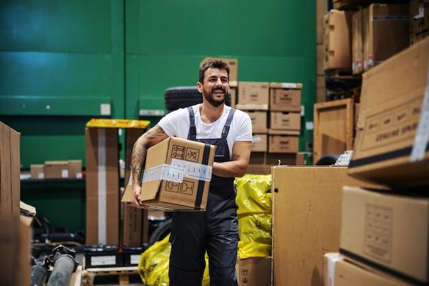 Hardwerkende, getatoeëerde, bebaarde handarbeider die door het magazijn loopt en een zeer zware grote doos draagt die klaar is voor export.