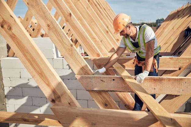 Hardwerkende man in een goed zichtbaar vest en een veiligheidshelm die een metalen hoek op een dakkarkas aanpast
