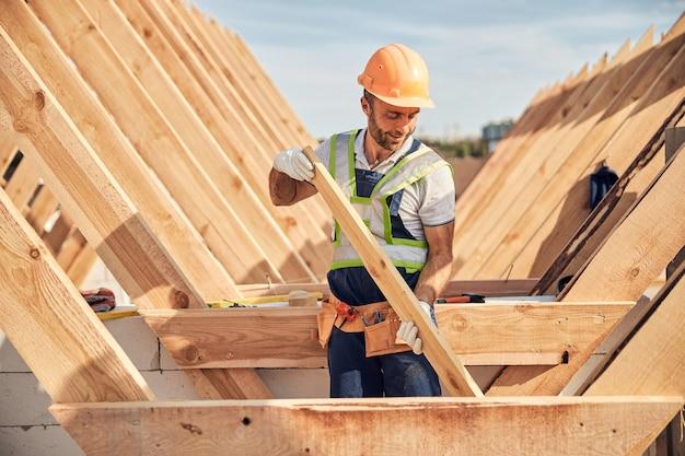 Hardwerkende man in een helm en handschoenen met een stuk hout voor het bouwen van een dak