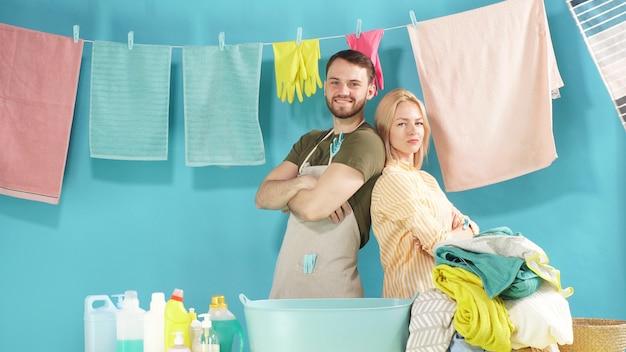 Hardwerkende paar staat klaar om u te helpen met wasserij. wasserette