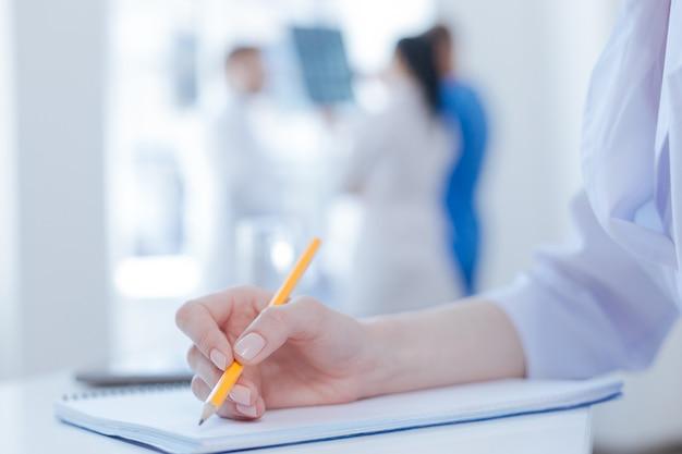 Hardwerkende professionele geconcentreerde arts die werkt en aantekeningen maakt terwijl andere collega's x ray scan achter bespreken