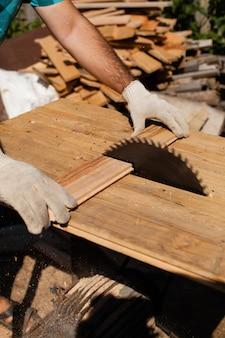Hardwerkende schrijnwerker die houten plank snijdt, focus op zaag