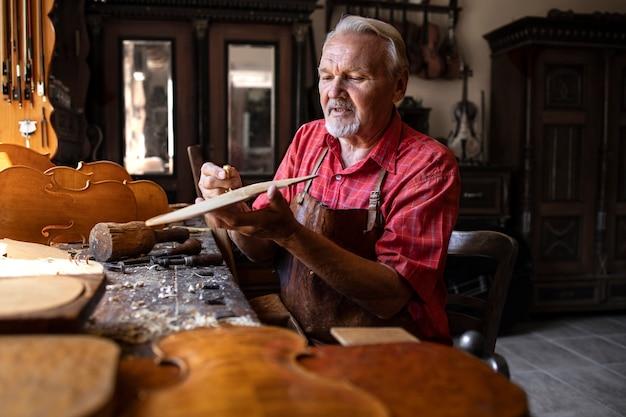 Hardwerkende senior timmerman bezig met zijn creatieve project in timmerwerkplaats