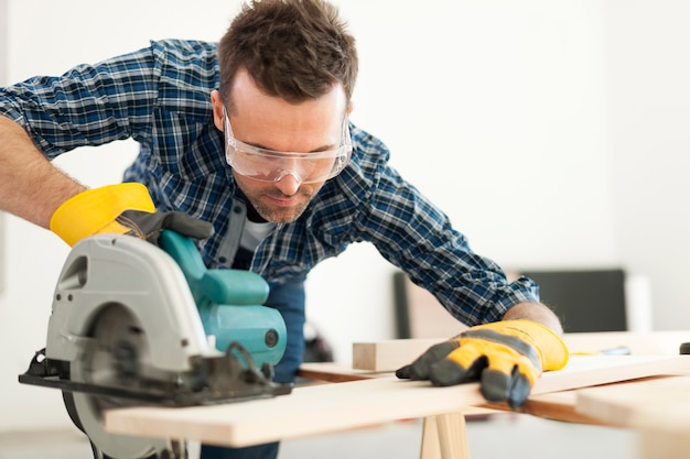 Hardwerkende timmerman die houten plank snijdt