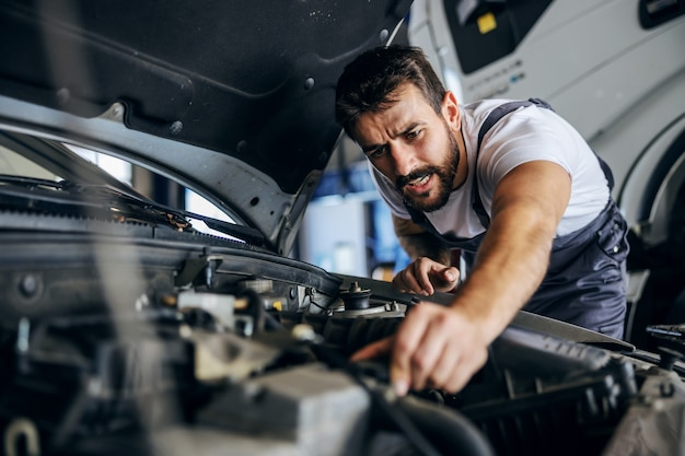 Hardwerkende toegewijde bebaarde werknemer in overall die auto repareert