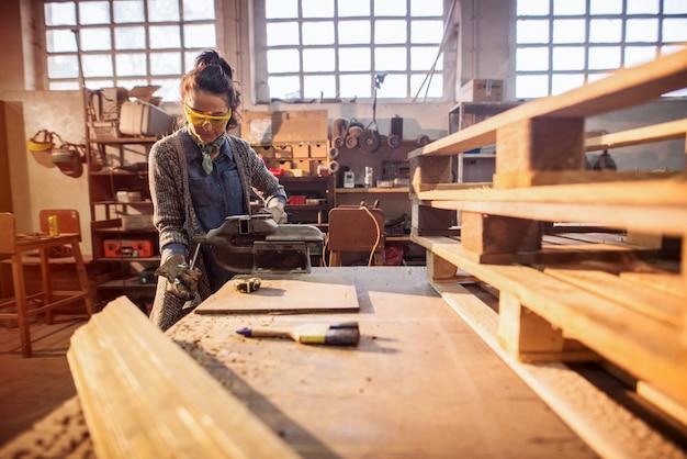 Hardwerkende vrouwelijke timmerwerk werknemer met stalen bankschroef op de tafel in haar atelier.