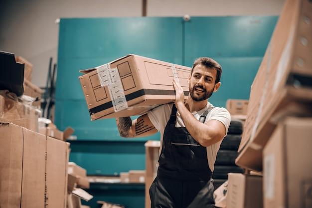 Hardwerkende werknemer die de doos op de schouder houdt en deze verplaatst terwijl hij in de opslag loopt.