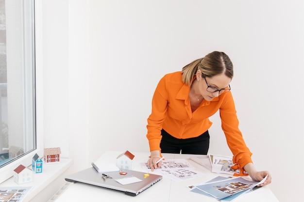 Hardworker-wijfje die aan blauwdruk op het werk werken