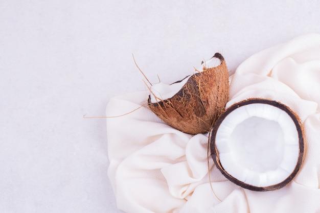 Harige kokosnoot in tweeën gebroken op wit tafelkleed.