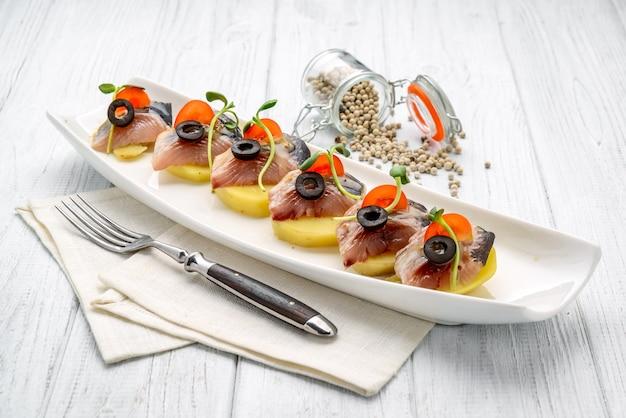 Haring canapé met aardappel en ui.