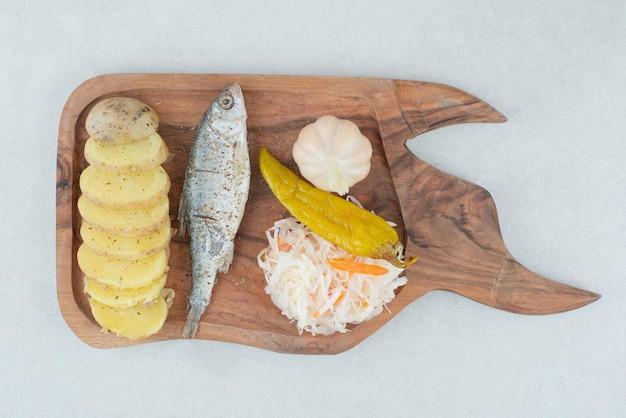 Haring, gekookte aardappelen en gemengde augurken op een houten bord.