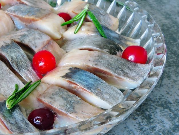 Haring met veenbessen en rozemarijn. stukken haring in een kristallen schaal.