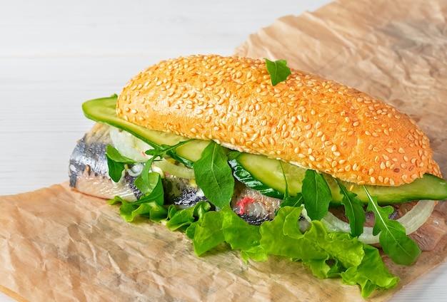 Haringhandel met ui, komkommer en salade op papier