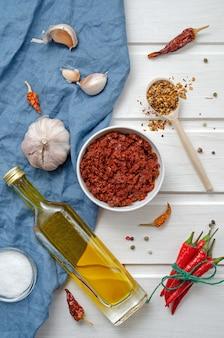 Harissa ingrediënten voor het koken van hete chili rode peper, grof zeezout, knoflook, komijnzira, olijfolie, gemalen koriander op een donkere leisteen tafel. adjika, muhammara. oosterse keuken.