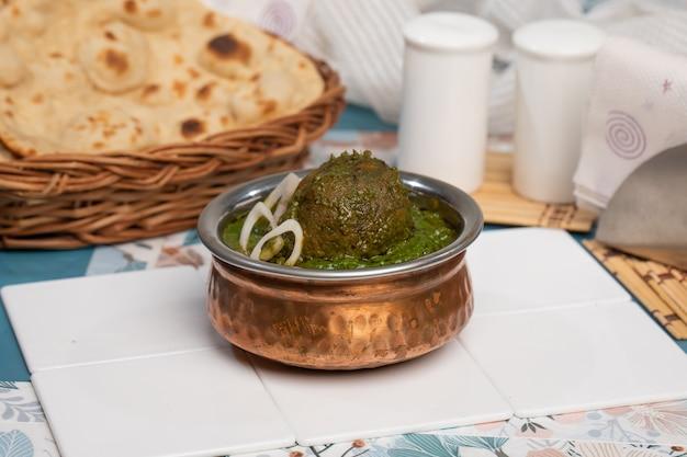 Hariyali kofta curry in kom op witte leisteen achtergrond. hariyali kofta is een gerecht uit de indiase keuken met gefrituurde balletjes van aardappel en paneerkaas in uien-tomatenjus met kruiden. indiaans eten.