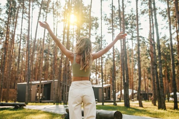 Harmonie. achteraanzicht van slanke jonge vrouw met lang blond haar die handen opsteekt naar de zon die op een mooie herfstdag in de natuur staat
