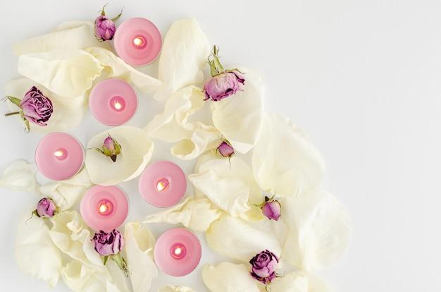Harmonie concept. brandende aromakaarsen, gedroogde rozen en bloemblaadjes op wit. plat leggen, ruimte kopiëren