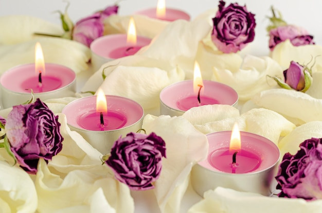 Harmonie en aromatherapie concept. brandende aromakaarsen, droge rozen en bloemblaadjesachtergrond.
