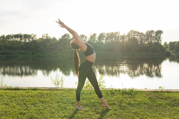 Harmonie en gezond levensstijlconcept - jonge slanke vrouw in sportkleding die yoga in openlucht beoefent.