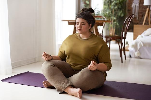 Harmonie, evenwicht, zen en vrede concept. binnen schot van plus grootte op blote voeten jonge brunette vrouw met haar broodje zittend op mat benen gekruist en ogen dicht, mediteren na yoga praktijk