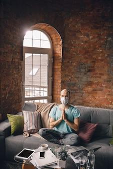 Harmonie. jonge man die thuis yoga doet terwijl hij in quarantaine zit en freelance online werkt.
