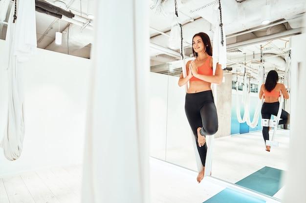 Harmonie leven. jonge blanke vrouw in sportkleding die vlieg- of luchtyoga beoefent in studio of sportschool, op het ene been in witte hangmat staat en mediteert, volledige lengte. wellness en een gezonde levensstijl