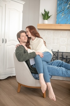 Harmonie. mooie vrouw met lang rood haar die een gelukkige, peinzende man knuffelt die samen in een fauteuil thuis zit
