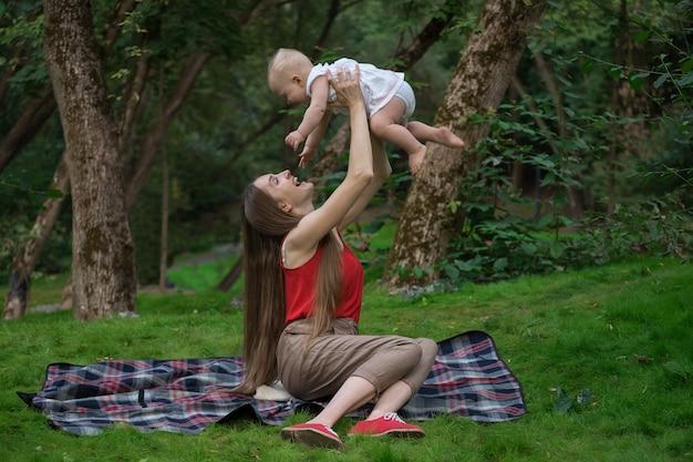 Harmonieuze familie buitenshuis. gelukkig liefhebbende moeder en haar baby. moeder speelt met kind