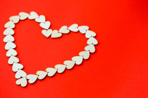 Hart bekleed met houten hartjes op een felrode achtergrond. plaats voor een inscriptie, romantische foto voor valentijnsdag