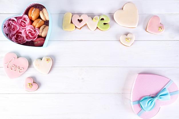 Hart doos met macarons en rose op witte houten achtergrond, valentijnsdag