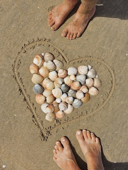 Hart en schelpen op zandmannetjes en damesvoeten