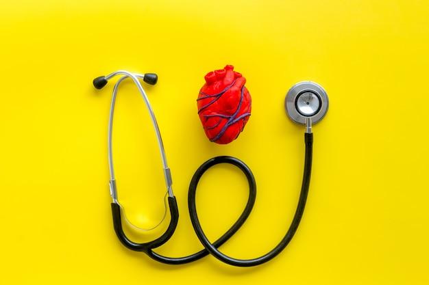 Hart en stethoscoop geïsoleerd op geel