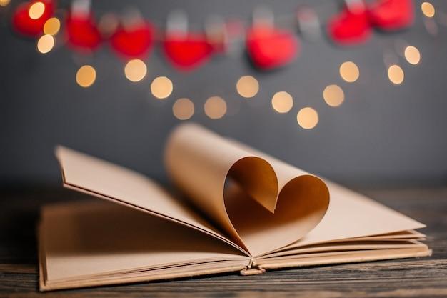 Hart gemaakt van boekbladen in licht, liefde en valentijn concept op een houten tafel