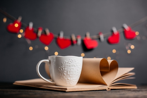 Hart gemaakt van boekbladen met een kopje in lichten, liefde en valentijn concept op een houten tafel