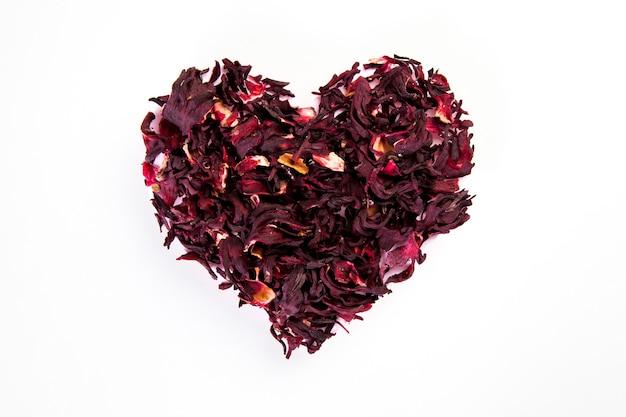 Hart gemaakt van gedroogde roselle bloem op witte muur, gezond leven en voedingsconcept