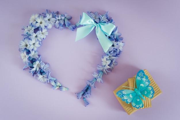 Hart gemaakt van hyacint bloemen met mint boog en geschenkdozen met vlinder op paarse achtergrond